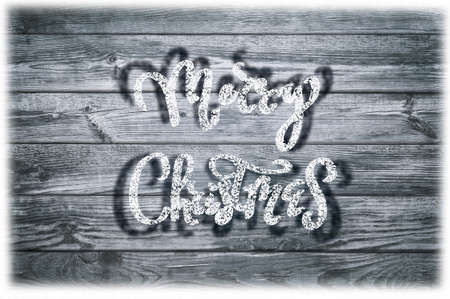 A snowy handwritten text on a wood background. Winter frozen background. Christmas background. Holidays.