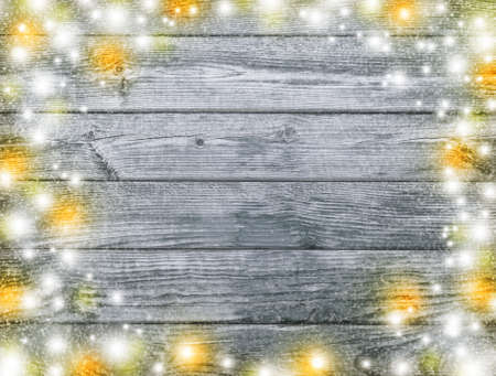 Celebratory lights on a gray wooden background. A festive party. Christmas background. New Year background. Old board texture.
