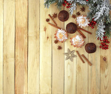 Festive homemade pastries on a wooden table. Snow-covered branches of the Christmas tree and pastries with spices. Aromas of holidays. Comfort. Christmas
