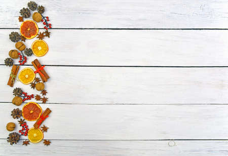 long Christmas ornament made of gingerbread, cones, cinnamon, nuts, anise stars, dried fruits on a wooden background. Christmas background in a rustic style. Top view. Home cosiness. Food background.