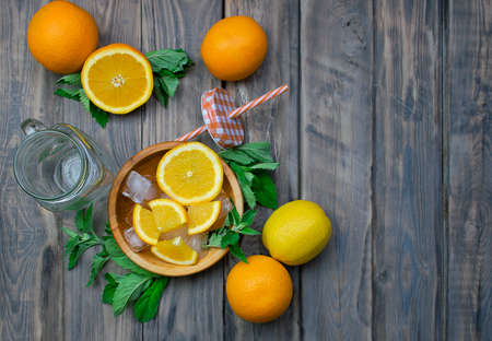 Preparation of summer refreshing fruit drinks. Citrus and aromatic herbs on a wooden table. The concept of a healthy diet and detoxification. Vitamins.