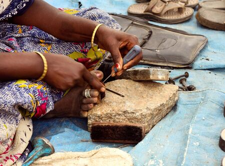 Skilful Indian woman repairing footwear on the street