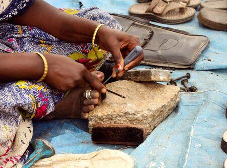 Skilful Indian woman repairing footwear on the street