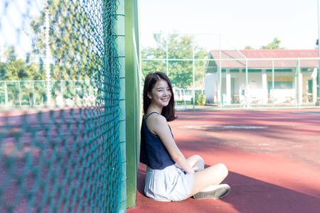 beautiful asian girl on tennis court after playing tennis with friend dressing like sport girl for sport, healthy, exercise, use purpose with artificial sun flares and color shift Stock Photo