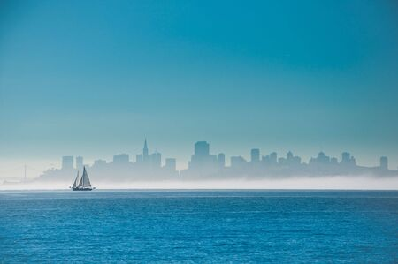 Yacht sailing on San Francisco Bay with the city skyline behind.