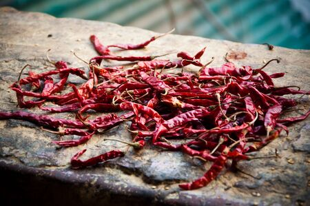 Red chilli peppers drying on a stone wall.