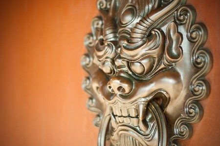 Traditional Chinese styled Lion Guardian ornamental door knocker in bronze.