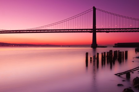 The Bay Bridge in San Francisco silhouetted against a clear sky just before sunrise.