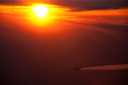 A Boeing 747 Jumbo Jet in flight against a setting sun.