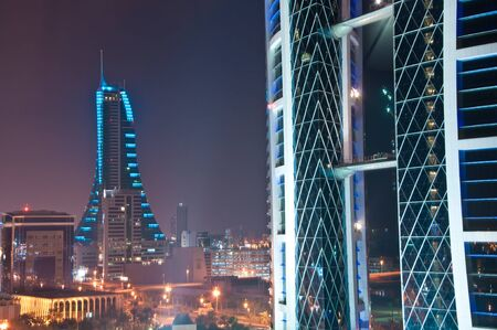 The World Trade Centre, Bahrain, at night and city lights beyond.