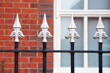 redbrick: Traditional wrought iron railing  fence outside a redbrick English home.