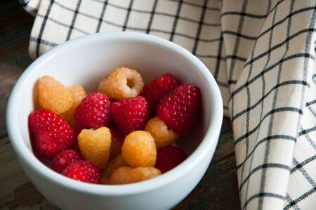 Fresh red and amber raspberries served in a white bowl on a breakfast tray  Stock Photo
