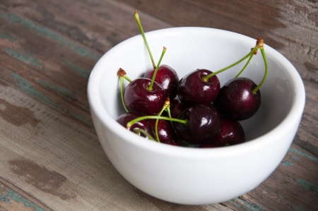 Fresh black cherries served in a white bowl on a breakfast tray