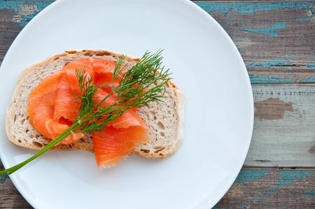 salmon ahumado: Salmón ahumado servido en pan de masa madre recién horneado con guarnición de eneldo fresco