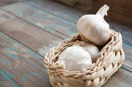 Fresh garlic bulbs in a small wicker basket served on an aged wooden tray