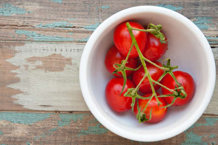 Fresh vine tomatoes in a white bowl on a natural wood background