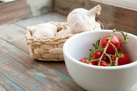 Fresh vine tomatoes in a white bowl along with a basket of fresh garlic  All served on a rustic wooden tray  Stock Photo
