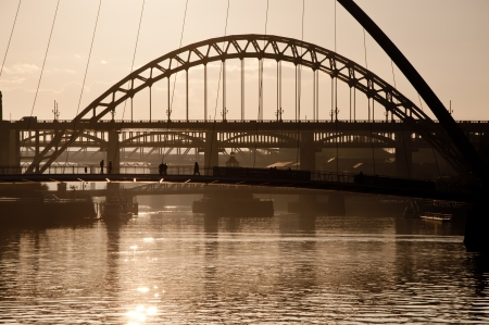 silhoutted: People crossing the Millenium Bridge over the River Tyne, Newcastle Upon Tyne, England  Silhoutted at dusk with the Tyne Bridge in the background