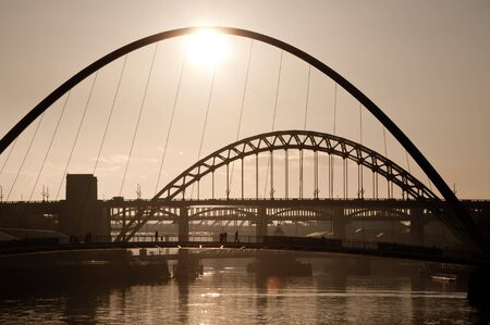 People crossing the Millenium Bridge over the River Tyne, Newcastle Upon Tyne, England  Silhoutted at dusk with the Tyne Bridge in the background  photo