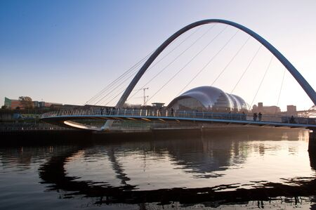 People cross the Millenium Bridge over the River Tyne in between Newcastle and Gateshead in England, UK