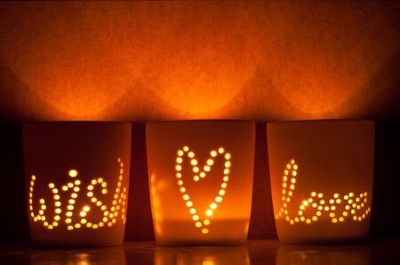 Candle lit cups with wish, love, and a heart shining through
