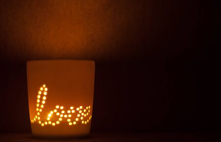 Candle lit cup with the message of love shining through
