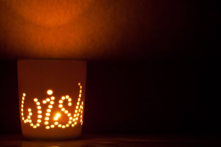 candle lit cup with the message of wish shining through