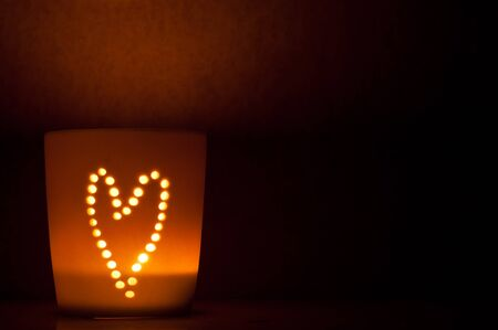 candle lit cup with the image of a heart shining through