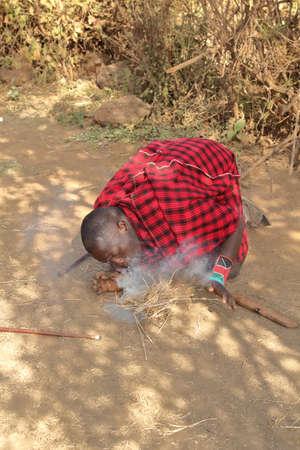KENYA, AMBOSELI NATIONAL PARK - AUGUST 04, 2018: The Maasai man makes a fire.