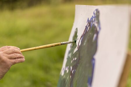 Drawing oil paintings of a natural landscape on a white cardboard