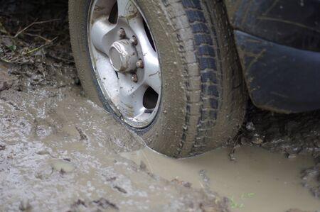 Car stuck, car wheel in a dirty puddle, rough terrain.