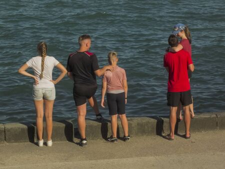 family stands on the coastal by the sea.