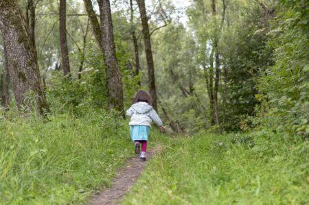 little girl runs away in the forest Foto de archivo