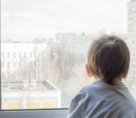 A little boy looks out the window. The street is bright and sunny. Cold weather