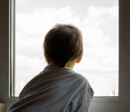 A little boy looks out the window. The street is bright and sunny. Cold weather Banco de Imagens