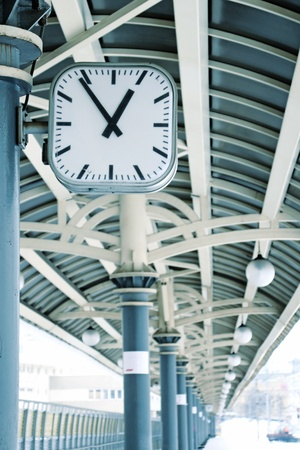 Clock on empty train station in winter. Arrows focused