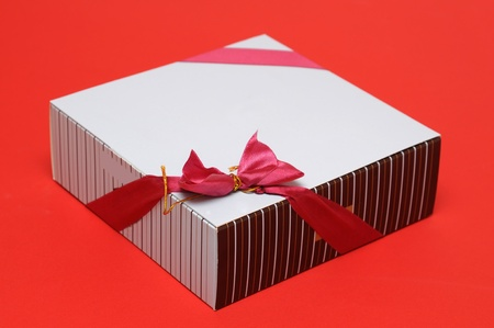 Square box of chocolate on red  photo