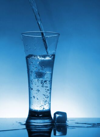 Water flows into the glass with ice photo