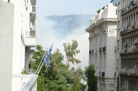 disperse:   ATHENS, GREECE - JUNE 15: 24-hour general strike against new $40.36 billion austerity program of tax hikes. police use tear gas to disperse demonstrators on June 15, 2011.