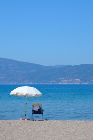 White umbrella and sunbed on a seashore  Stock Photo - 11371829