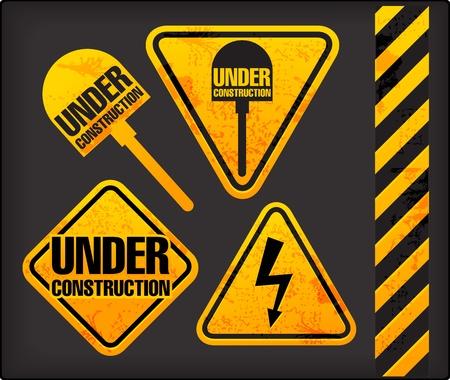 caution sign: In costruzione. Segni Grunge con l'illuminazione e la vanga