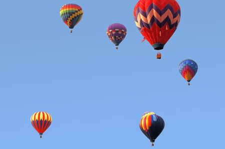 several balloons against a blue sky