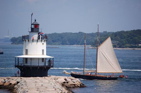 schooner: schooner sailing past a lighthouse