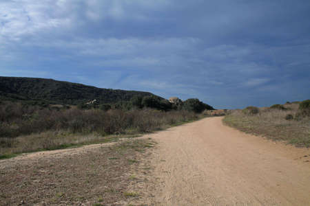 dirt road with gray clouds