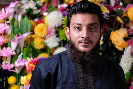 Dhaka, bangladesh, august 2017- portrait of a young man sells natural flowers at his own shops located at shavar in dhaka in bangladesh taken on 17 august, 2017