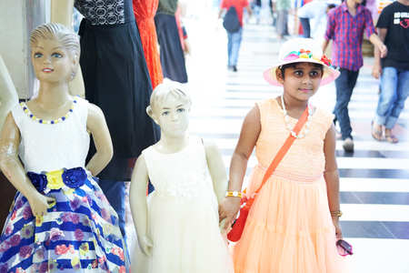 Dhaka, bangladesh, august 2017- a girl with hat is holding hand of a doll for taking pictures located at shavar shopping market in dhaka in bangladesh taken on 17 august 2017 Editorial