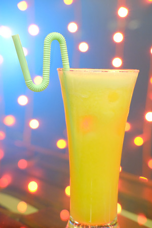 a glass of orange juice with straw on natural out of focus background