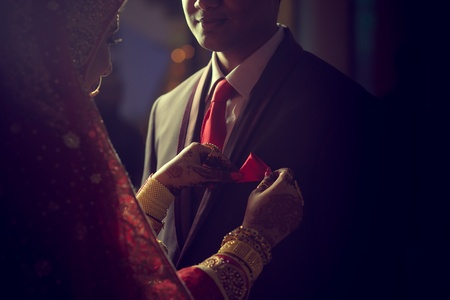 Stunning Indian bride looks at groom with passion while they stand in darkness