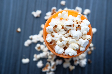 Popcorn on ornage blow on dark wood background.