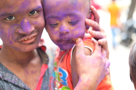 Holi celebrations - Closeup of sibling playing Holi in India. Stock Photo